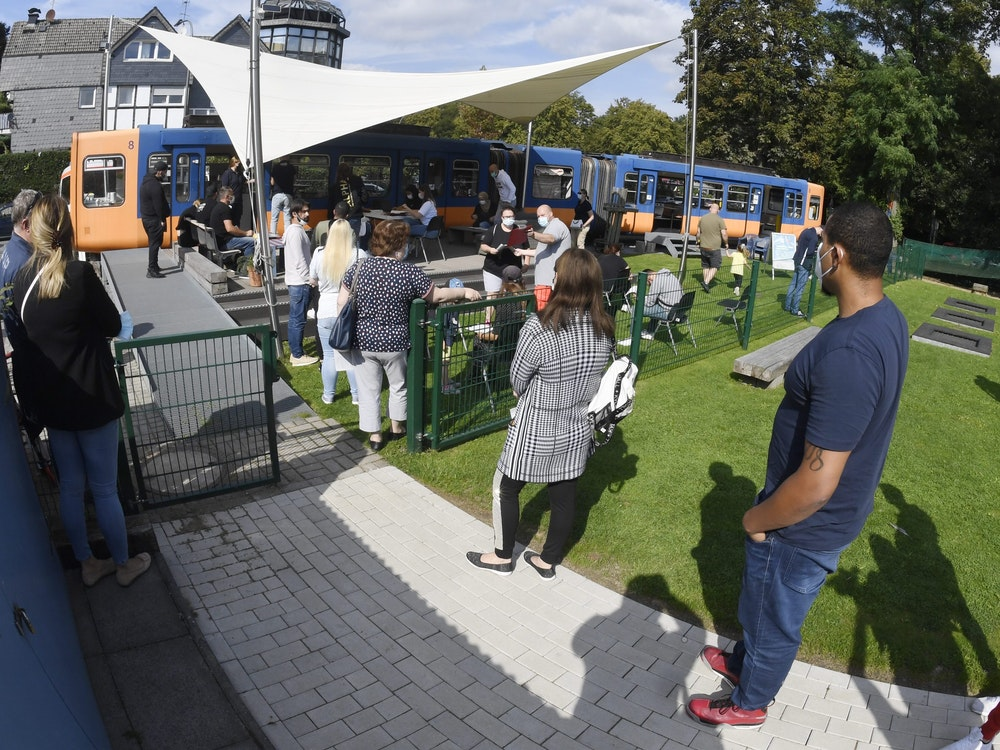 Menschen stehen am 12.09.2021 für die erste Impfung gegen Corona in einem stillgelegten Schwebebahnwagen auf einem Spielplatz Schlange. Impfwillige können sich dort bei der Sonderaktion ohne Anmeldung impfen lassen.