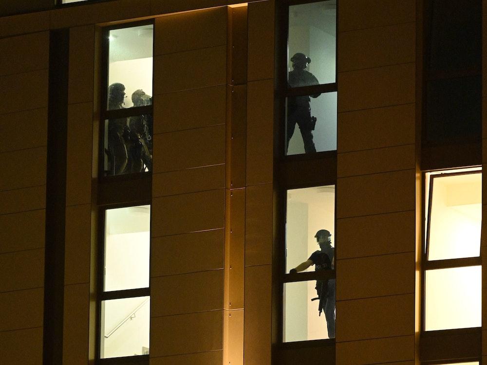 Spezialkräfte der Polizei sind im Einsatz in einem Düsseldorfer Hotel. Durch die Hotelfenster sind die Silhouetten der Beamten zu sehen, die das Gebäude durchsuchen.