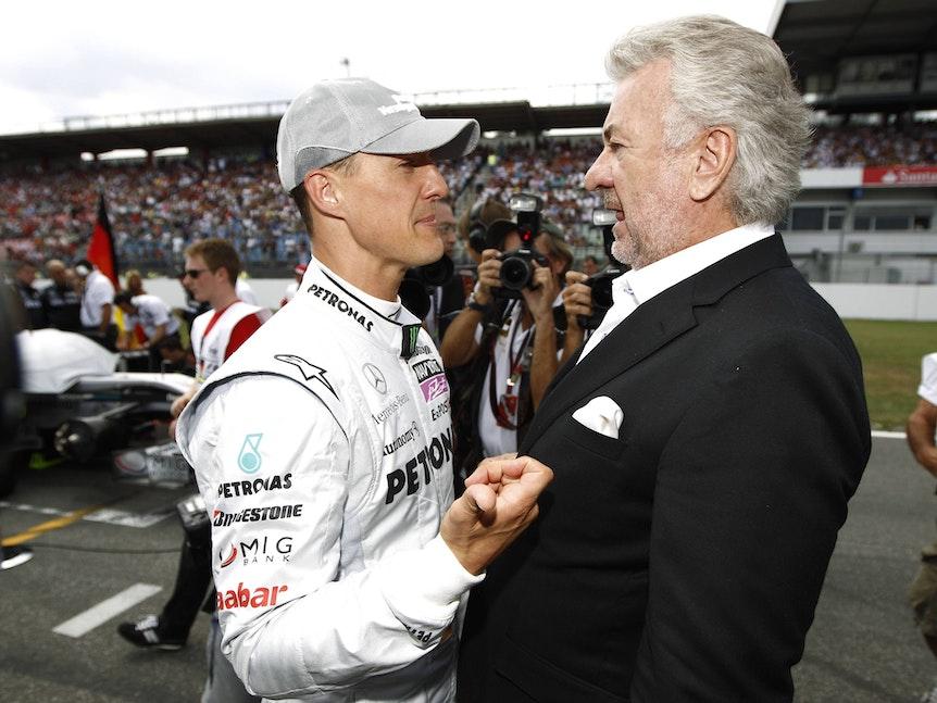 Michael Schumacher und Willi Weber stehen nah aneinander und schauen sich an.