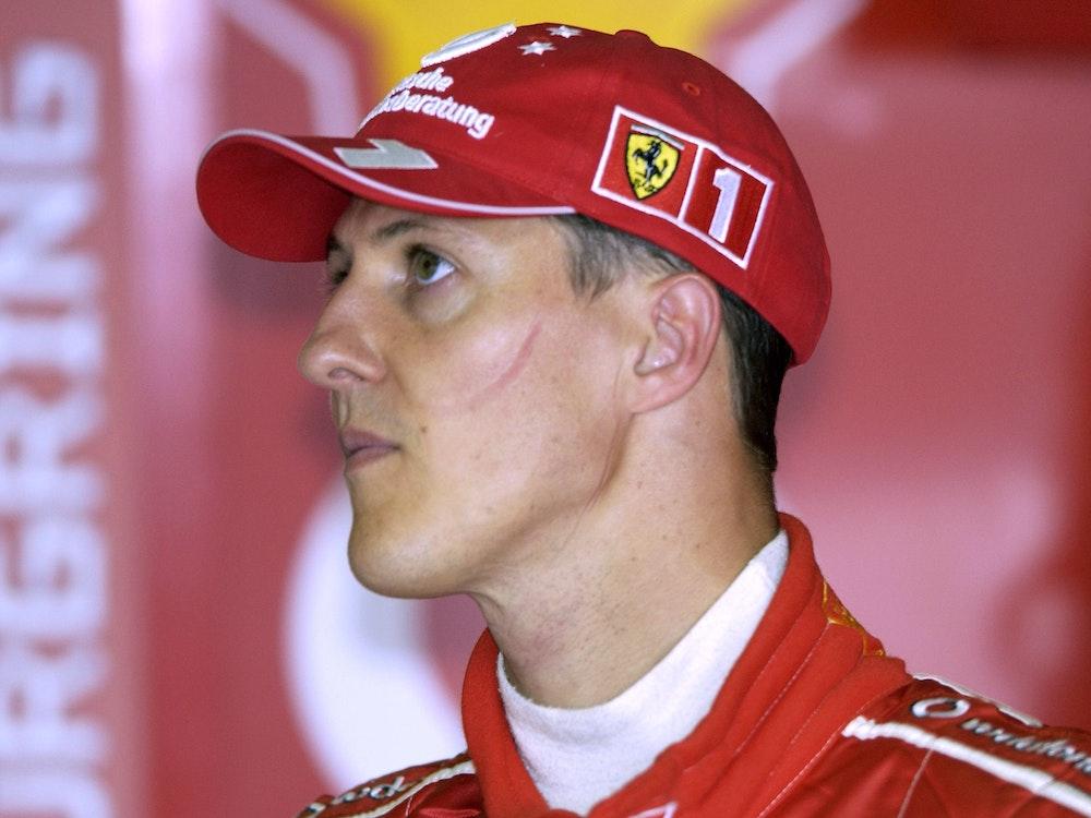 Michael Schumacher trägt einen roten Ferrari-Anzug eine rote Ferrari-Kappe.