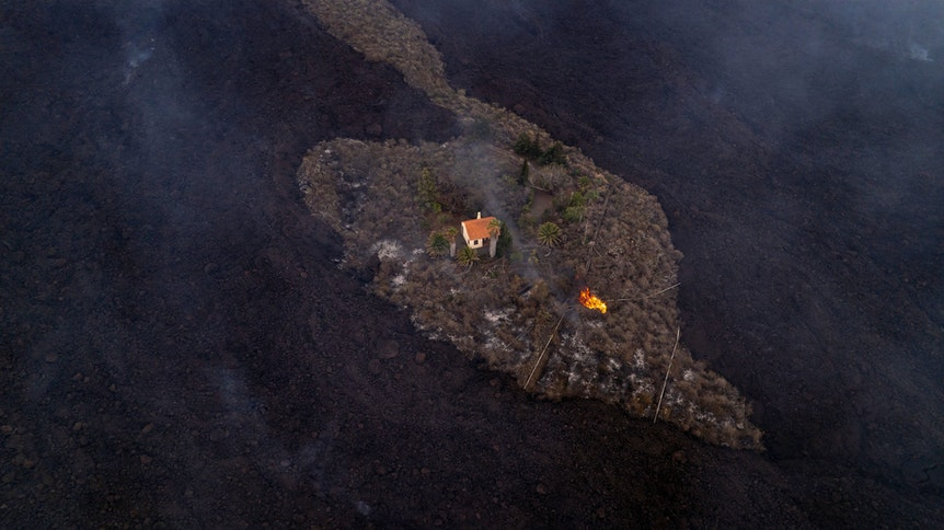 Auf diesem von iLoveTheWorld zur Verfügung gestellten Foto bleibt ein Haus intakt, während Lava fließt, nachdem ein Vulkan in der Nähe von Las Manchas auf der Insel La Palma ausgebrochen ist. Der Vulkan war am 19. September erstmals seit 50 Jahren wieder aktiv geworden.