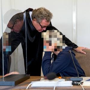 Angeklagte und Anwalt unterhalten sich im Gericht.