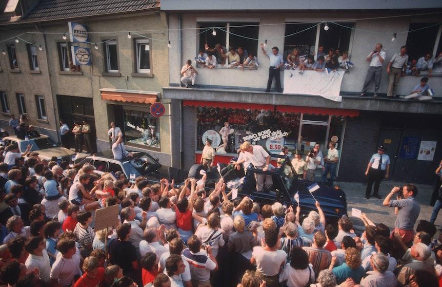 Boris Becker in einem Auto zwischen zahlreichen Fans