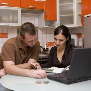Ein Ehepaar sitzt am Tisch und prüft die Finanzen. Ausblick Oktober 2021: Das ändert sich für Verbraucher.