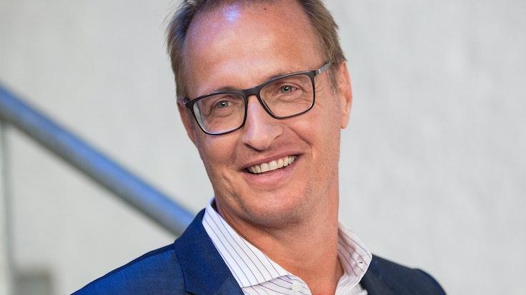 Moderator Florian König lächelt in die Kamera.