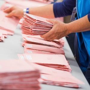 Wahlhelfer in Köln sortieren die roten Wahlbriefe mit den abgegebenen Stimmen für die Bundestagswahl 2017. Bei der diesjährigen Bundestagswahl berichten mehrere Städte über Rekordwerte bei den Briefwahlanträgen.