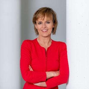 Katja Horneffer steht mit verschränkten Armen an eine Säule gelehnt und lächelt.