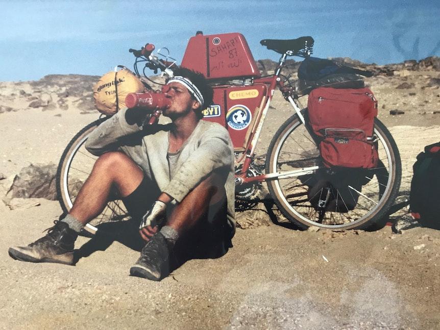Dieter Wolfs Sohn sitzt in der Wüste vor einem Fahrrad und trinkt.