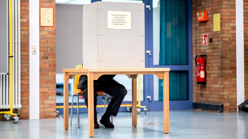 Ein Wähler sitzt in einem Wahllokal, das im Foyer einer Grundschule untergebracht ist, in der Wahlkabine und füllt seinen Stimmzettel für die Kommunalwahl aus.