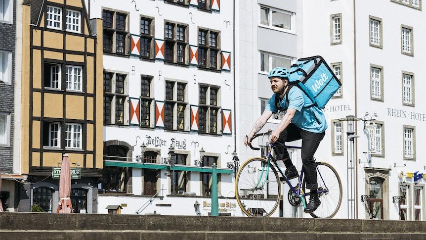 Ein Fahrer des finnischen Lieferdiensts Wolt fährt mit einem Fahrrad in Köln.