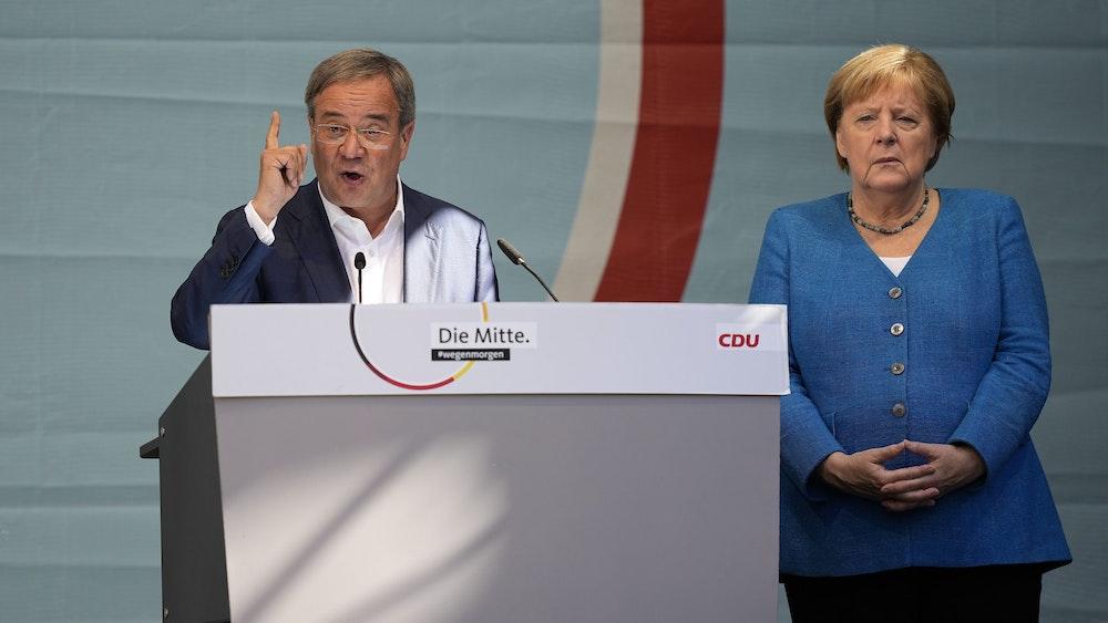 CDU-Kanzlerkandidat Armin Laschet und Noch-Kanzlerin Angela Merkel bei ihrem gemeinsamen Wahlkampfauftritt am Samstag, 25. September, in Aachen. Laschet spricht ins Mikro, Merkel steht daneben.