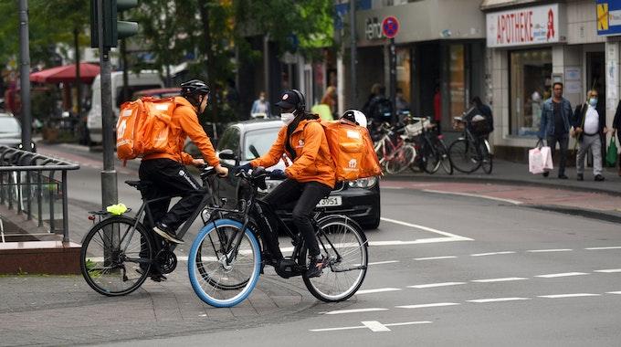 Zwei Lieferando-Fahrer fahren auf der Venloer Straße in Köln.