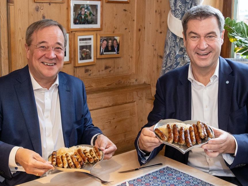 Markus Söder (r), CSU-Parteivorsitzender und Ministerpräsident von Bayern, und Armin Laschet, Unions-Kanzlerkandidaten, CDU-Vorsitzender und Ministerpräsident von Nordrhein-Westfalen, essen zusammen in einem Bratwurst-Restaurant Nürnberger Würstchen.