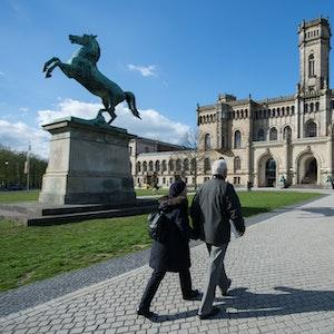 Zwei Passanten gehen auf einem Fußweg zur Leibniz Universität.