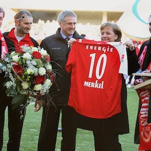Angela Merkel hält ein Cottbus-Trikot mit der Nummer 10 hoch, Tomislav Piplica hält einen Blumenstrauß in den Händen.