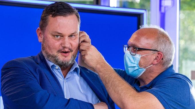 Rene Domke, Spitzenkandidat der FDP für die Landtagswahl in Mecklenburg-Vorpommern, am 14. September vor einem Rededuell des NDR. Ein Mitarbeiter steckt ihm einen Knopf ins Ohr.