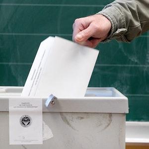 Ein Wähler wirft seinen Stimmzettel am 26. September 2021 in einem Wahllokal in die Wahlurne in Duisburg.