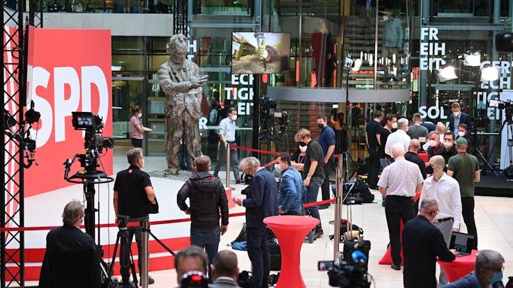 Journalisten stehen in der SPD-Parteizentrale vor der Skulptur von Willy Brandt.
