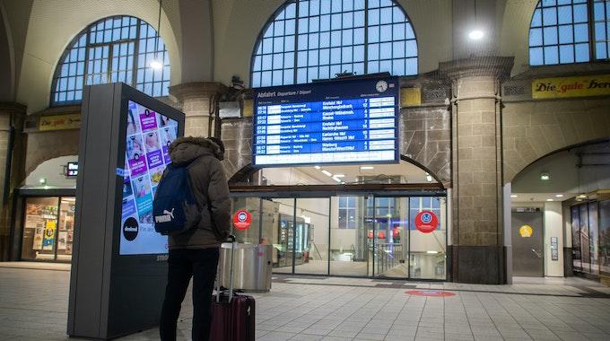 Ein Mann steht im Hauptbahnhof vor der Anzeigetafel, auf der Verspätungen und Zugausfälle angezeigt werden, und schaut auf sein Smartphone.