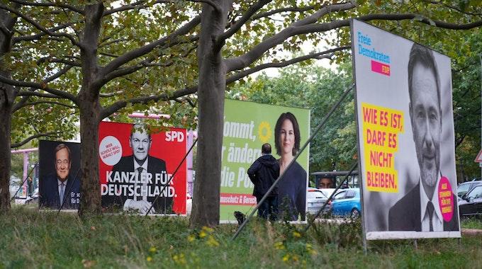 Wahlplakate der SPD mit Olaf Scholz, von Bündnis 90/Die Grünen mit Annalena Baerbock und der FDP mit Christian Lindner stehen auf einer Straße nebeneinander.