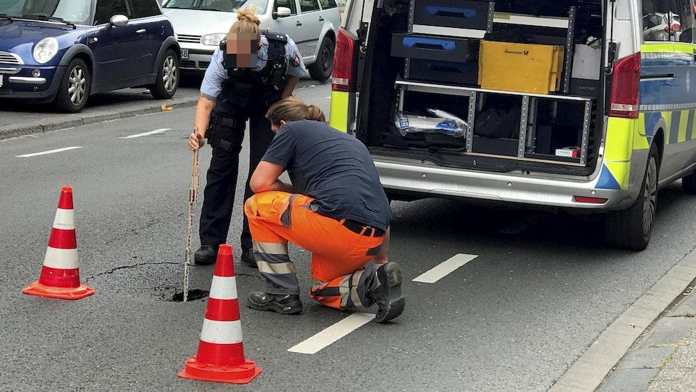 Eine Polizistin hält einen Zollstock in das Loch in der Fahrbahn.