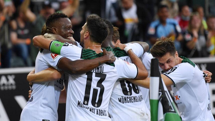 Denis Zakaria und Lars Stindl (v.l.) liegen sich im Arm und bilden mit anderen Spielern von Borussia Mönchengladbach eine Jubeltraube am 25. September 2021.