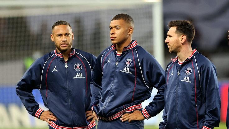 Neymar, Kylian Mbappe und Lionel Messi stehen in Trainingsjacken auf dem Feld. Neymar und Mbappe haben die Hände in den Hüften.