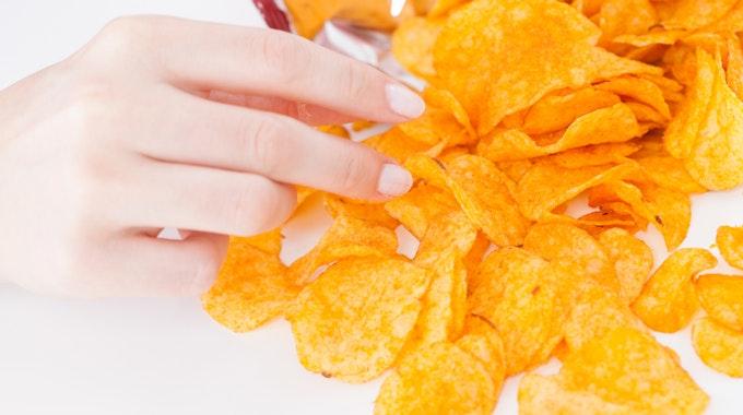 Das Symbolfoto zeigt eine Hand, die nach Kartoffelchips greift.