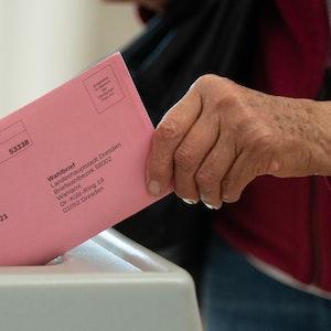 Eine Frau wirft in einem Briefwahlbüro ihren Wahlschein in einer Wahlurne.