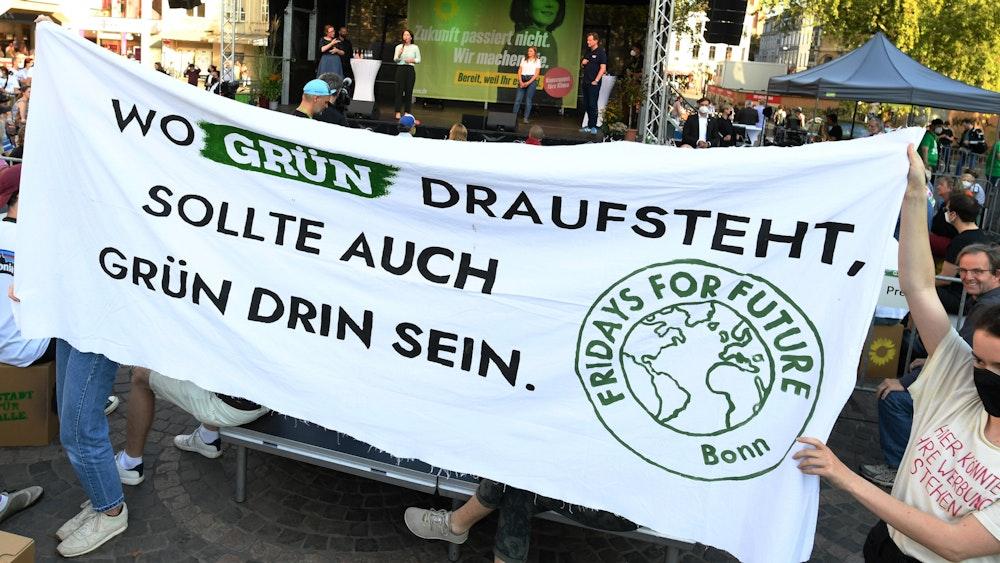 Aktivistinnen von Fridays for Future halten ein Transparent mit der Aufschrift «Wo Grün draufsteht, sollte auch Grün drin sein.», während der Rede von Annalena Baerbock (hinten).