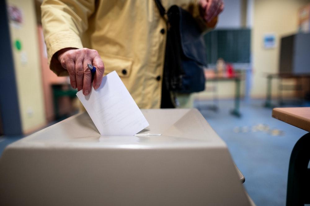 Eine Frau wirft einen Wahlschein in eine Wahlurne.