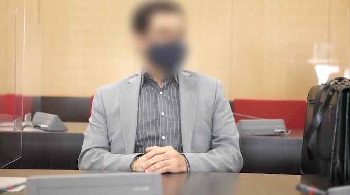 Der angeklagte Arzt sitzt mit Maske im Saal des Landgerichts.