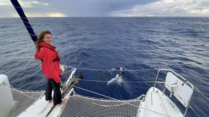 Mara Bergmann steht auf einem Katamaran, vor ihr schwimmen Delfine im Meer.