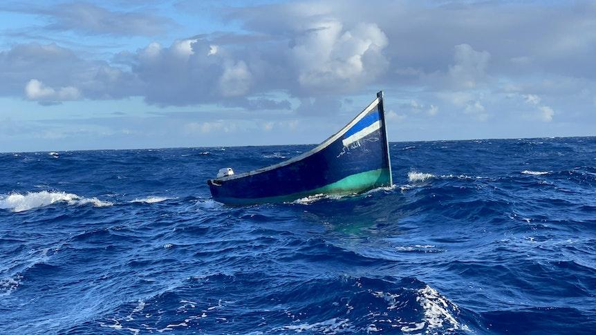 Ein Holzboot treibt auf dem Meer.