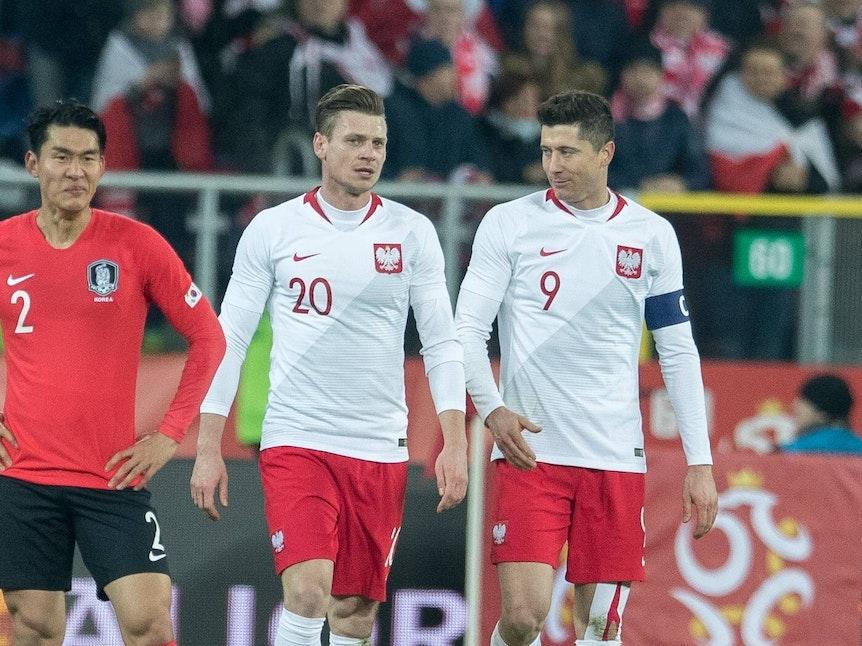 Lukasz Piszczek und sein Kollege Robert Lewandowski gehen gemeinsam über das Feld, links von ihnen steht ein südkoreanischer Spieler.