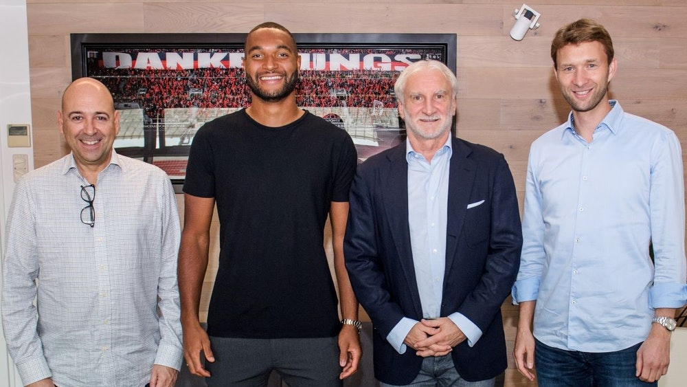 Jonathan Tah posiert zusammen mit Geschäftsführer Fernando Carro, Rudi Völler und Simon Rolfes vor einem Bild, das im Stadion aufgenommen worden ist.