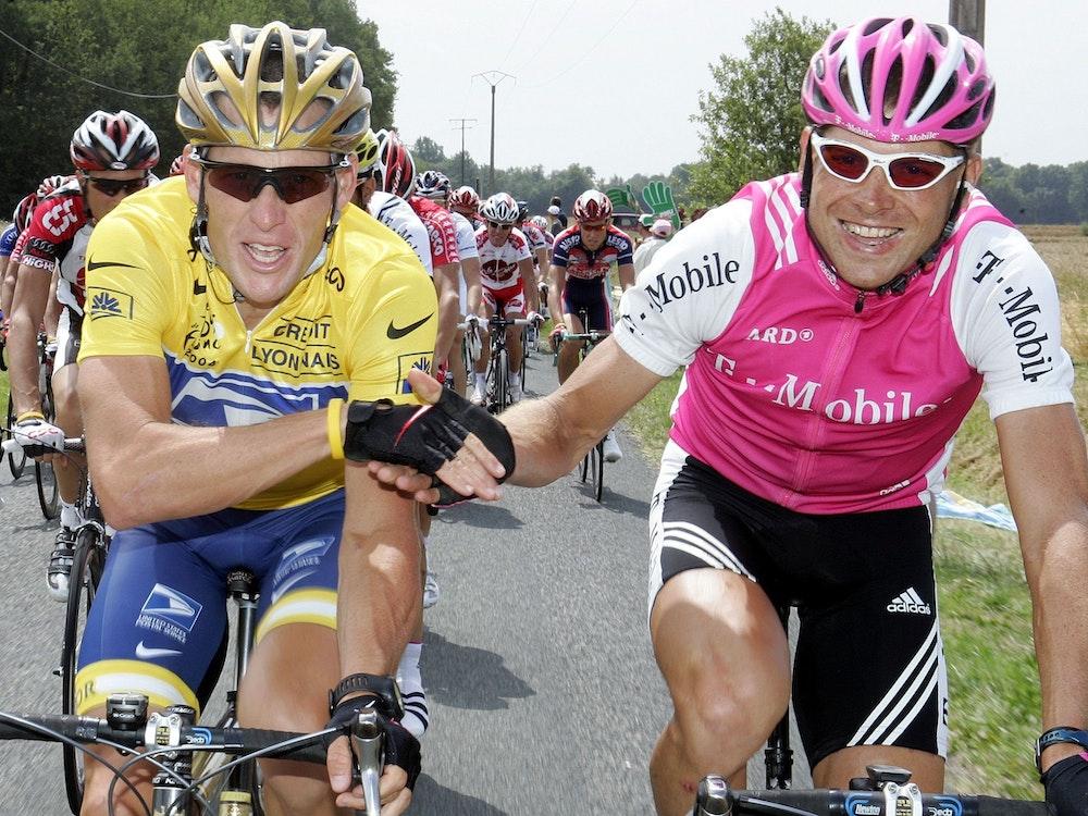 Der deutsche Radprofi Jan Ullrich reicht dem späteren Tour de France-Sieger Lance Armstrong aus den USA auf der Schlussetappe 2004 die Hand.
