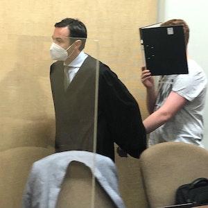 Der Anwalt hält seinen Mandanten an der Hand und lotst ihn in den Gerichtssaal.