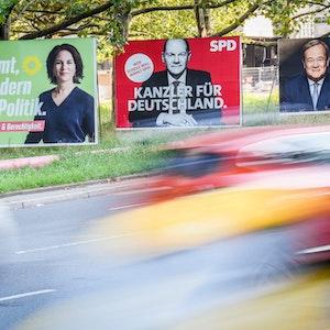 Berlin: Autos fahren an Wahlplakaten von Bündnis 90/Die Grünen, SPD und CDU vorbei.