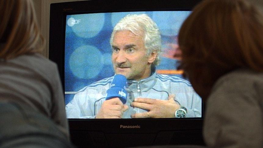 Zwei Kinder schauen in einer Hamburger Wohnung im Fernsehen ein Interview mit dem Teamchef der deutschen Fußball-Nationalmannschaft, Rudi Völler, in Reykjavik.