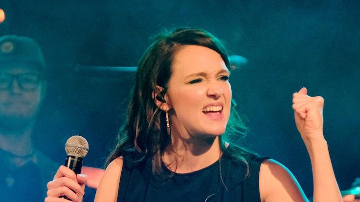Carolina Kebekus steht mit einem Mikrofon in der Hand auf einer Bühne.