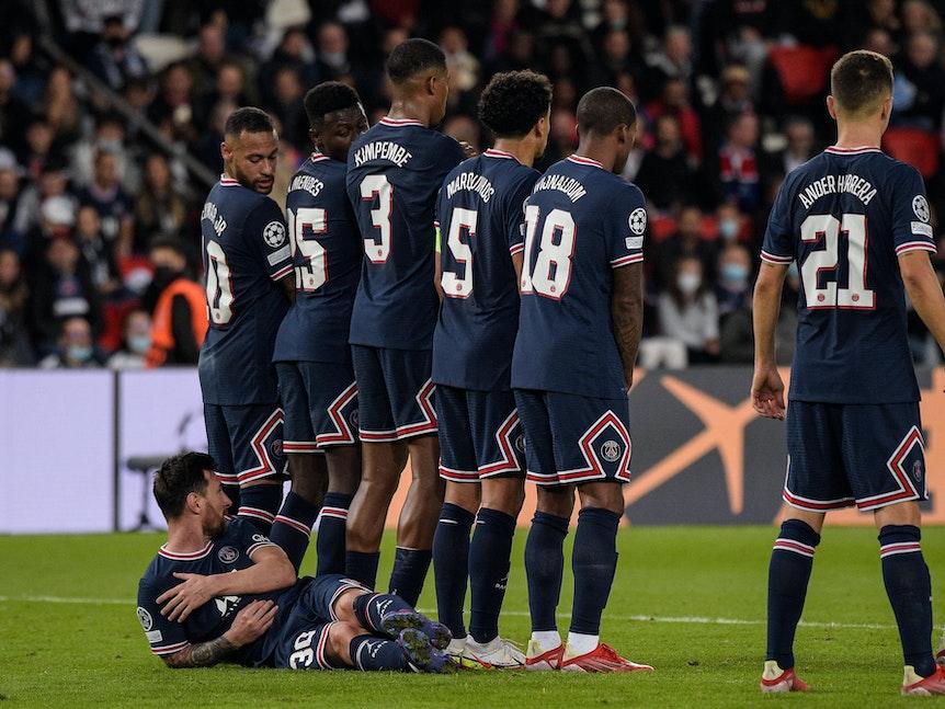 Lionel Messi liegt hinter der Mauer, Neymar schaut zu ihm runter