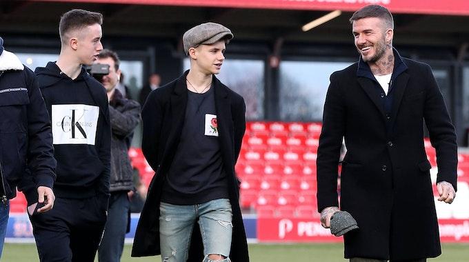 Romeo Beckham und David Beckham gehen auf dem Fußballplatz entlang.