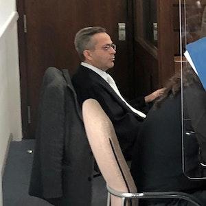 Köln: Der Angeklagte sitzt im Gerichtssaal und verdeckt sein Gesicht mit einer Akte.