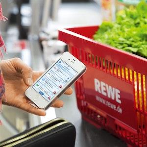 Das Symbolfoto zeigt eine Frau an der Kasse von Rewe. Sie hält ein Smartphone in der Hand mit einer Payback App.