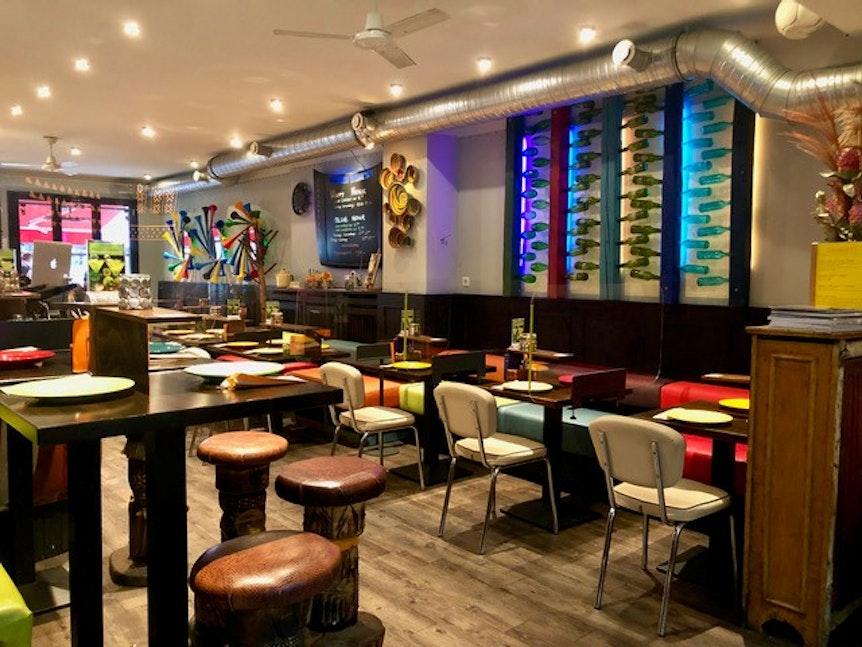 Der Innenbereich des Restaurants besteht aus bunten Tischen und Stühlen.