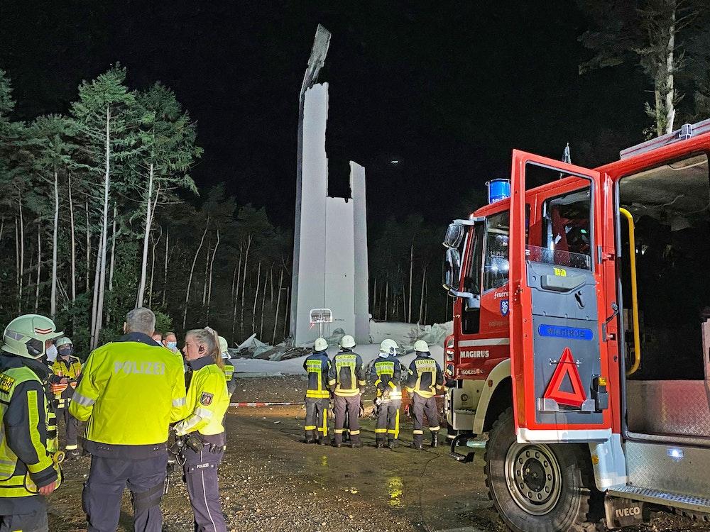 Feuerwehrleute und Polizisten stehen am 29. September 2021 vor den Resten des Turms eines Windrandes. Das fast 240 Meter hohe Windrad ist in sich zusammengestürzt.