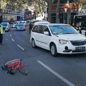 Ein zerfetztes Fahrrad liegt auf der Fahrbahn, Polizisten sichern Spuren.