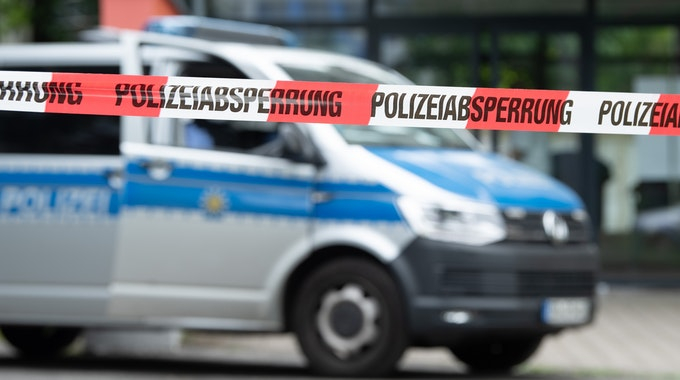 Ein Polizeiauto steht im Juni 2021 hinter einer Absperrung in Dresden.