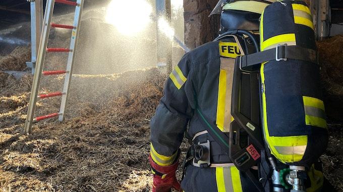 Ein Feuerwehrmann löscht brennendes Stroh.
